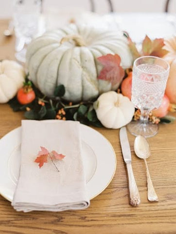 Table setting featuring pastel pumpkins, plus and a small leaf on a folded white napkin for a fall baby shower