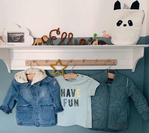 Clothing hooks in a toddler room that hold toddler-sized jackets and t-shirts.
