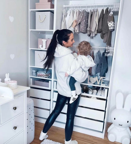 Mom and toddler looking at clothing hanging in an open closet.