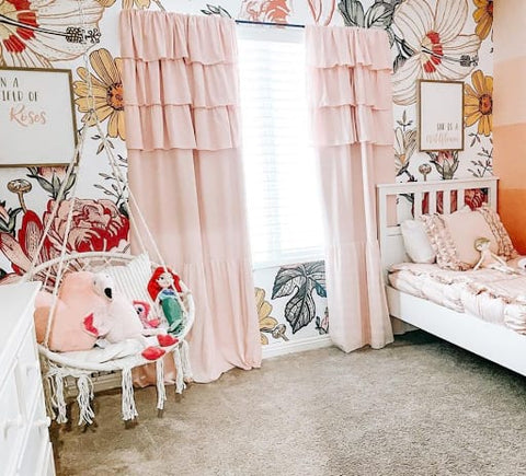 Toddler bedroom with floral print wallpaper, pink curtains, and a white wicker swing hanging from the ceiling.
