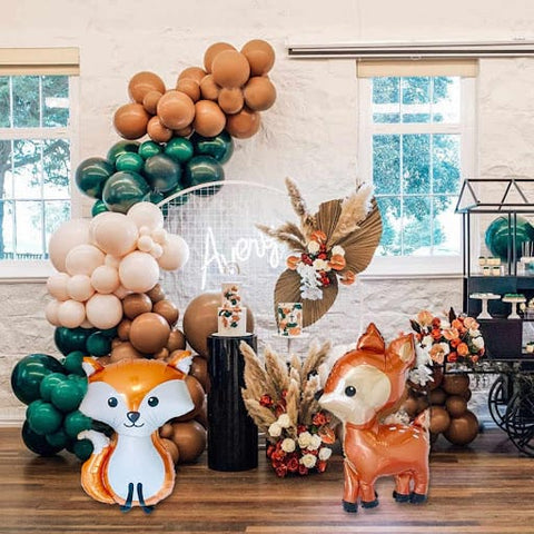Emerald green, cream, brown, and fox and deer balloons on display for a fall baby shower