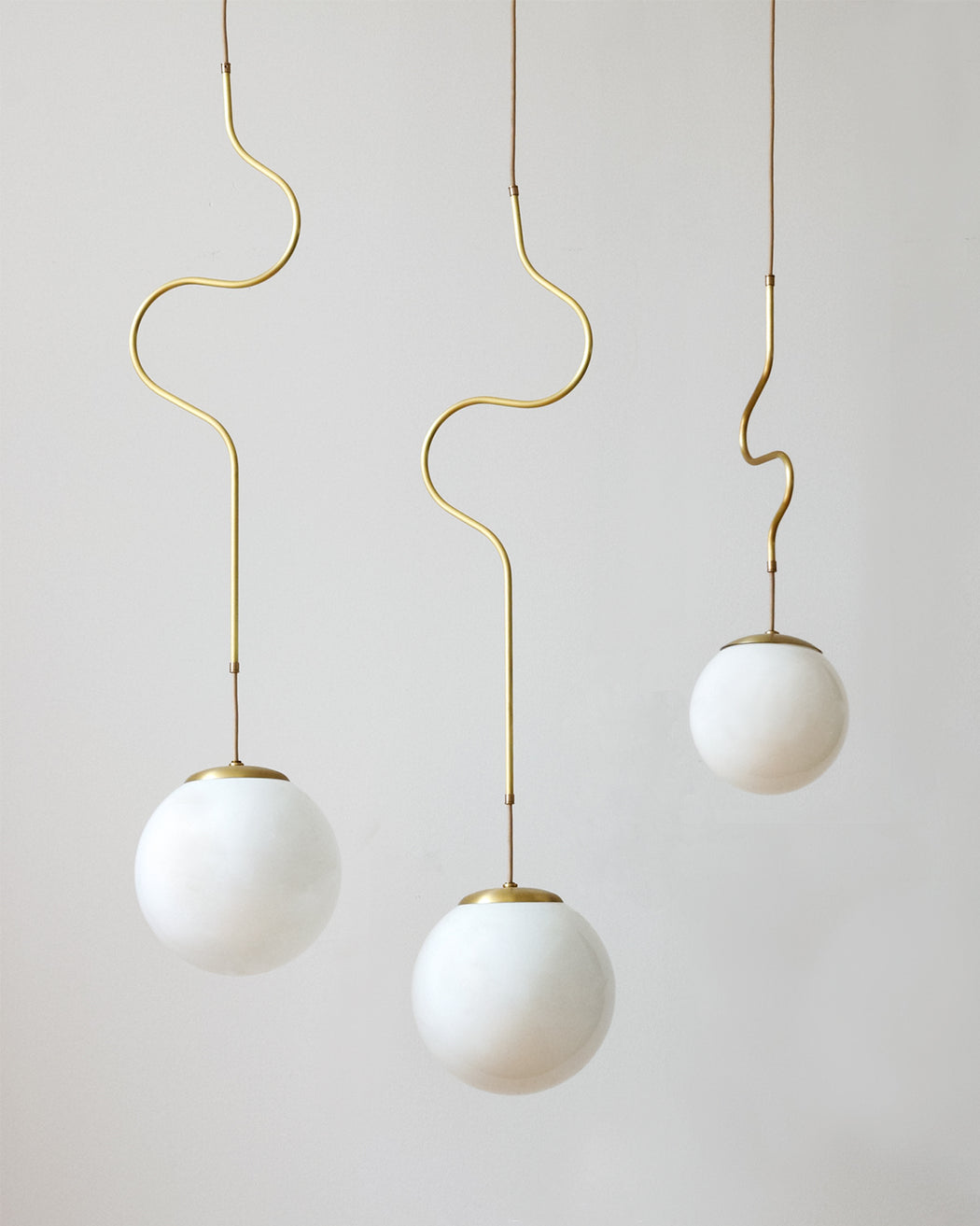 Satin brass Contour ceiling pendant lights made by Lostine in Philadelphia, Pennsylvania.  Satin brass modern lighting design with white glass globe.  Hardwired light fixture.  Simple interior design, made in the USA.