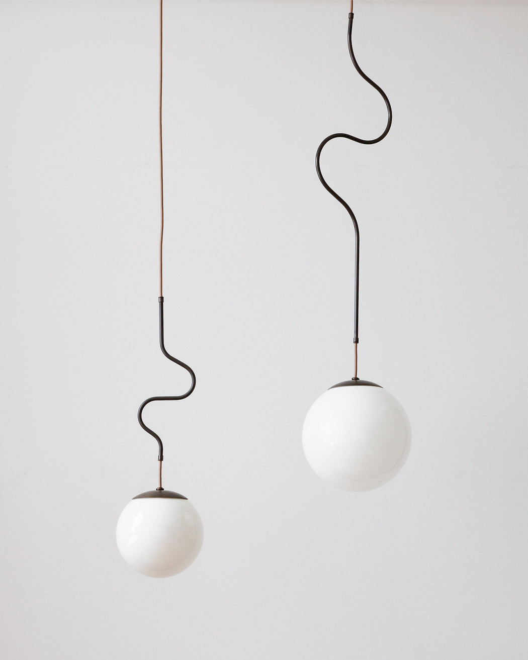 Oil rubbed bronze Contour ceiling pendant lights made by Lostine in Philadelphia, Pennsylvania.  Oil rubbed bronze modern lighting design with white glass globe.  Hardwired light fixture.  Simple interior design, made in the USA.