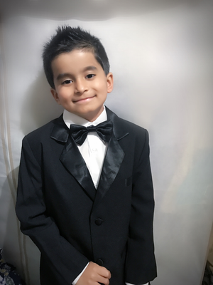 little boy wearing a handsome black tuxedo
