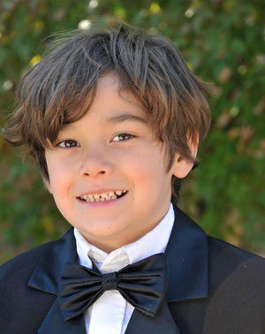 little boy wearing tuxedo for photo