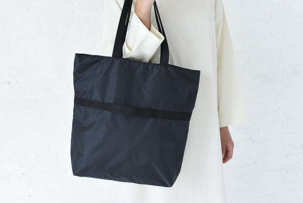 Dual function, quality tote bag. Made of 100% ripstop nylon, the bag can easily switch from a shoulder bag to the hand bag by folding in the middle and using the attached trim handles. Unlined with one interior pocket, perfect for everyday use and travel. Made in USA.