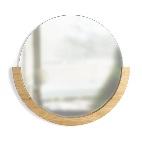 Modern and minimalist round wall mirror with natural wood frame bottom half by Umbra at Port of Raleigh
