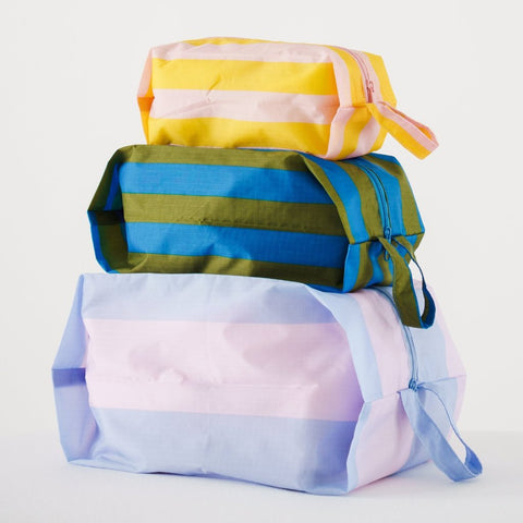 Simple, durable, and lightweight - this set of three bright striped zippered pouches by Baggu are perfect for travel and home organization.