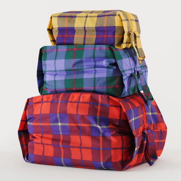 Simple, durable, and lightweight - this set of three tartan plaid zippered pouches by Baggu are perfect for travel and home organization.