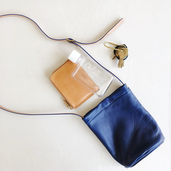 Simple minimalist leather cross body purse with adjustable straps made of natural leather in Houston Texas by Julia Gabriel. Bucket style semi-circle design in soft supple leather and hard base for standing upright on it's own. Vegetable tanned leather straps and interior pockets.