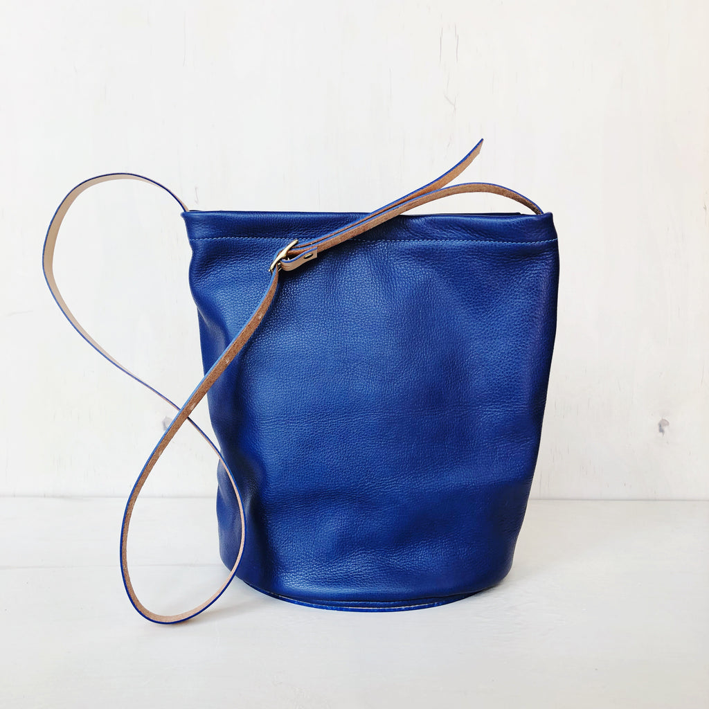 Simple minimalist leather cross body purse with adjustable straps made of natural leather in Houston Texas by Julia Gabriel. Bucket style semi-circle design in soft supple leather and hard base for standing upright on it's own. Vegetable tanned leather straps and interior pockets. at Port of Raleigh