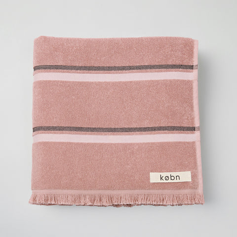 Modern striped bath, pool, beach towel with soft terry fabric on face and plain weave reverse framed by raw fringe detail on each end. Australian design by KOBN towels, inspire by Copenhagen, made in Turkey