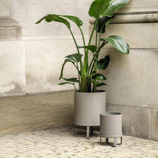 industrial, bauhaus inspired plant stands made from galvanized steel. Powder coated in muted solid colors, has a drain hole and a four legged stand. Come in two sizes. Danish design by Ferm Living.