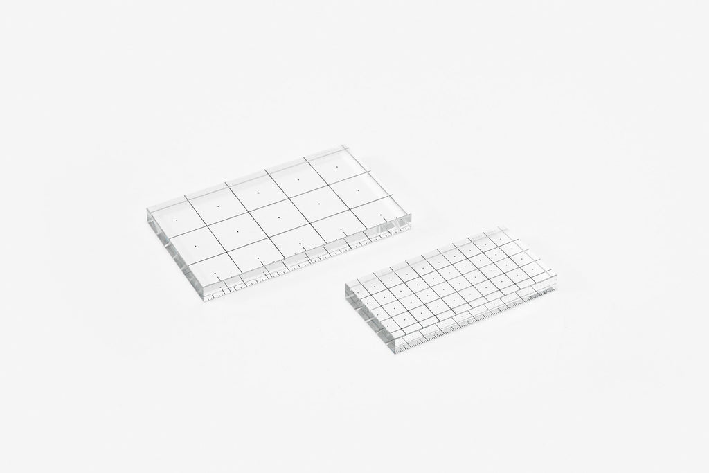 A modern glass ruler (centimeter or inches). Draw and measure with accuracy using this crystal glass ruler featuring a grid overlay that allows for precise alignment when placed above an existing drawing. By Areaware at Port of Raleigh