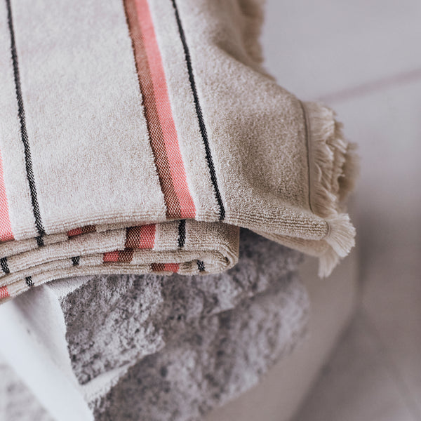 Modern striped bath, pool, beach towel with soft terry fabric on face and plain weave reverse framed by raw fringe detail on each end. Australian design by KOBN towels, inspire by Copenhagen, made in Turkey at Port of Raleigh