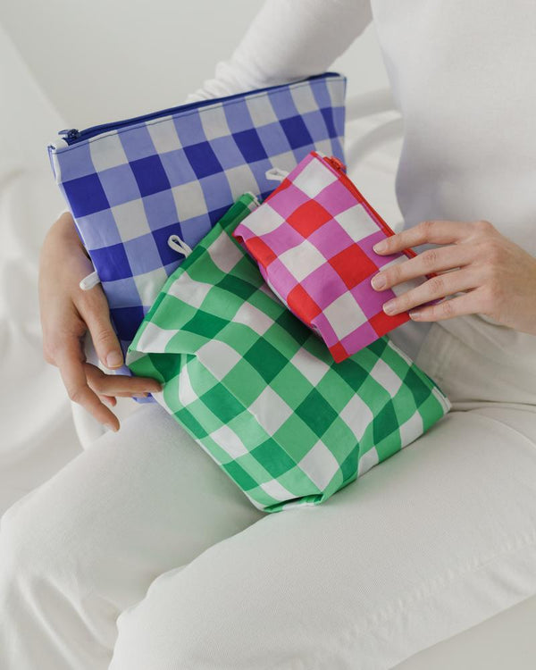 Go Pouch travel and organization zip pouches sold in a set of three with small, medium, large. Made of thick durable nylon by Baggu. Now in a summer-rich checkered pattern.