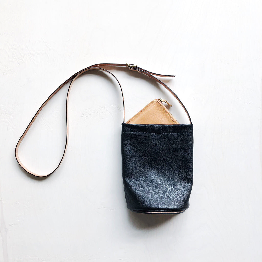 A brilliantly designed leather crossbody bag with a semicircle base shape for close and comfortable wear against the body. Black supple leather with a thick vegetable-tanned strap and sewn-on base makes this bag both sleek and simple enough for everyday use. Created in a mini size to keep traveling light easy and stylish.   at Port of Raleigh