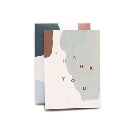 Say Thank You with this muted paint strokes card from Iowa based studio, Moglea. Copper foil stamped and comes with a patterned envelope. at Port of Raleigh