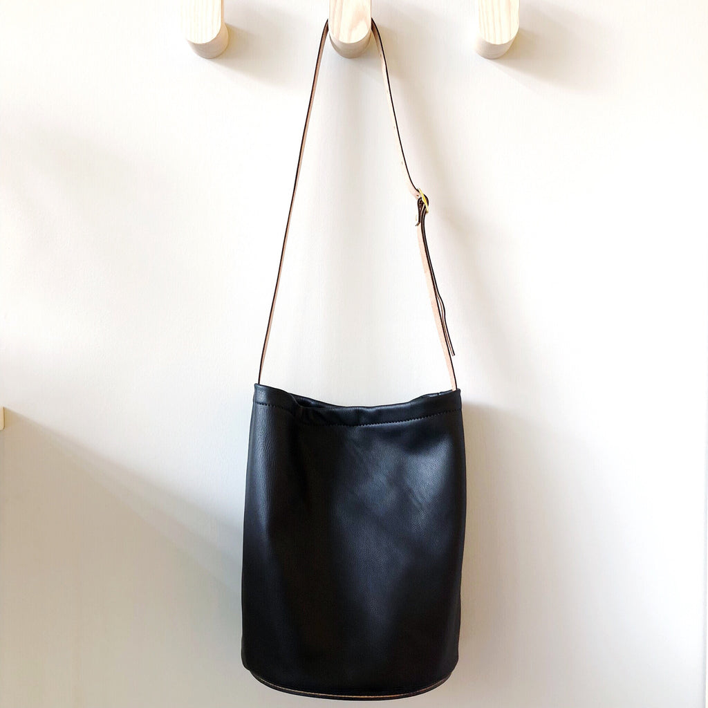 A brilliantly designed leather crossbody bag with a semicircle base shape for close and comfortable wear against the body. Black supple leather with a thick vegetable-tanned strap and sewn-on base makes this bag both sleek and simple enough for everyday use. Created in a medium size for carrying everyday things without loading you down.   at Port of Raleigh