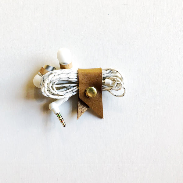 Beautifully colored leather and brass come together to keep your tech cords organized and detangled. Small but functional and well-made, these leather cord keepers work to keep your tech functional and clean.