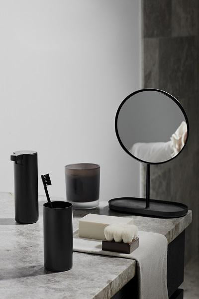 A sleek, simple, and modern mirror for your bathroom vanity. Designed with a tray base for holding loose items, and swivel mirror for multiple viewing angles. Made of black titanium coated steel, it is durable, and resistant to corrosion and scratches. Modern, sleek, and simply functional, part of the Modo collection from Blomus. Designed in Germany.