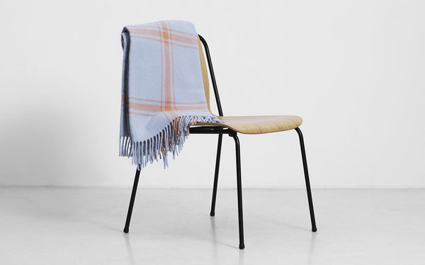 Lambswool blanket with a modern take on a classic style, woven with a check pattern with fringe tassels on the ends. Perfect size for wrapping up solo or cozy sharing. Made in Latvia by Normann Copenhagen.
