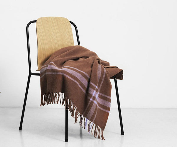 Lambswool blanket with a modern take on a classic style, woven in a framed pattern with fringe tassels on the ends. Perfect size for wrapping up solo or cozy sharing. Made in Latvia by Normann Copenhagen. at Port of Raleigh