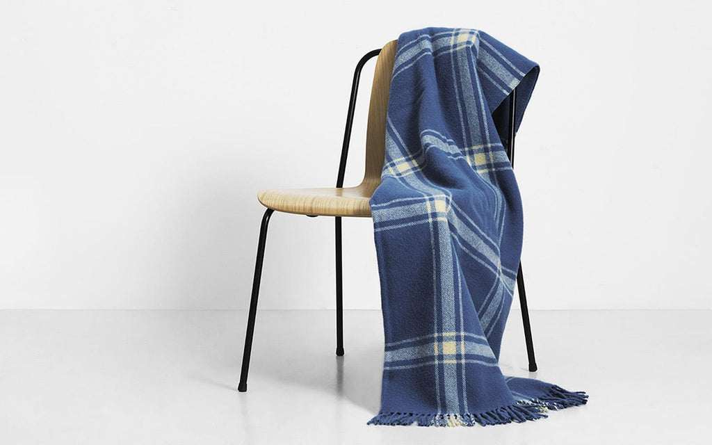 Lambswool blanket with a modern take on a classic style, woven with a check pattern with fringe tassels on the ends. Perfect size for wrapping up solo or cozy sharing. Made in Latvia by Normann Copenhagen. at Port of Raleigh