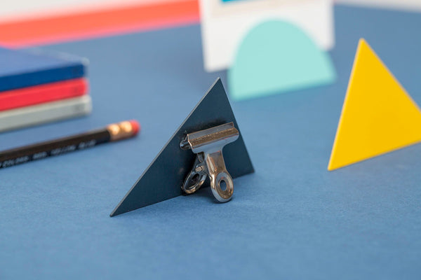 Photo Clips featuring modern shapes for enhancing your paper goods. Made with powder coated steel in the UK, use these on your desktop to hold business cards or memos, or on your shelves to display cards and art.