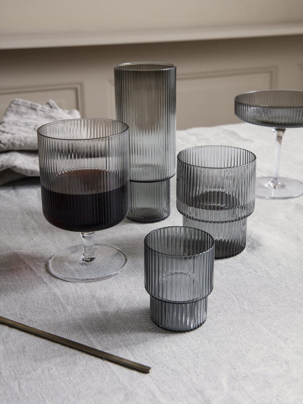 Simple, functional, and elegant drinking glasses, each with the rim at a different level, moulded with a rippled texture in a smoke colored glass. The perfect serving companion for a modern dining experience. Danish design by Ferm Living.