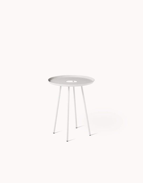 A simple and minimal side table with clever details. Made of fine sand coated steel, it has a hole in the middle to function as a handle for easy transporting, and for organizing cords. Designed by Dims.