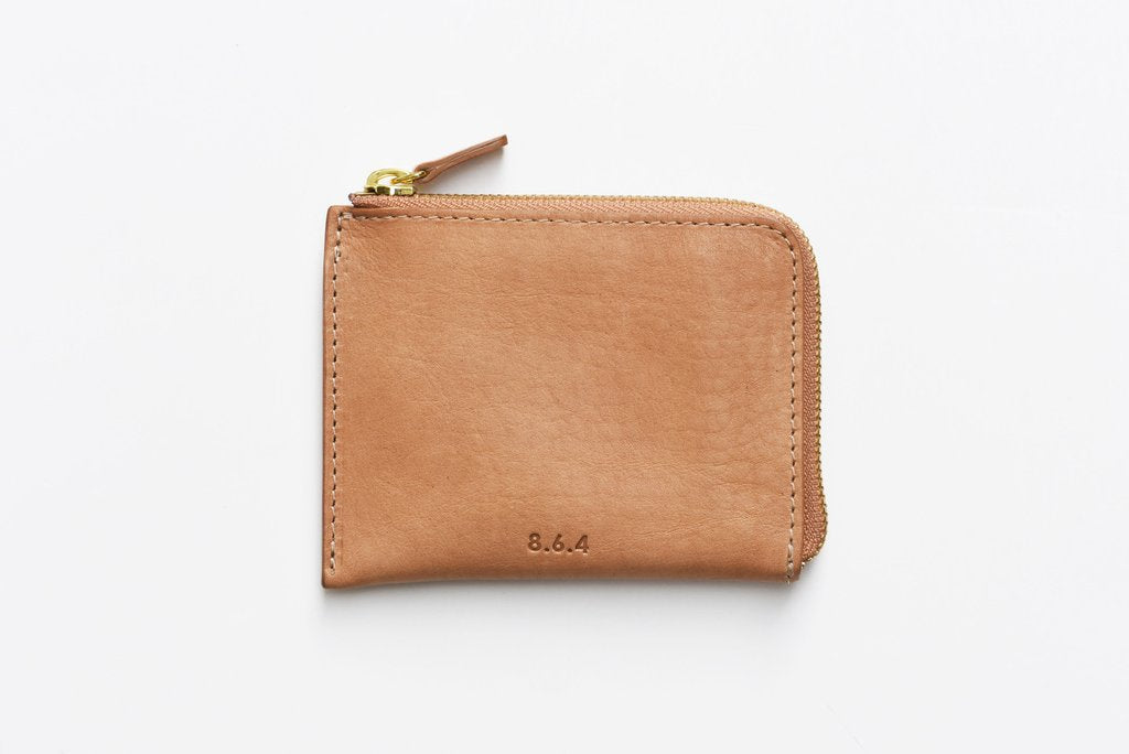 A wallet for light days, travelling, and the staunch minimalist. Made in NYC with vegetable tanned leather, this simple but lovely textured zip wallet can still fit more than its fair share of cash, cards, and even coins. at Port of Raleigh