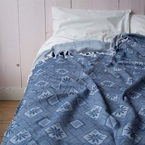 Dark blue cotton bedspread/tablecloth with fringes in a geometric pattern.