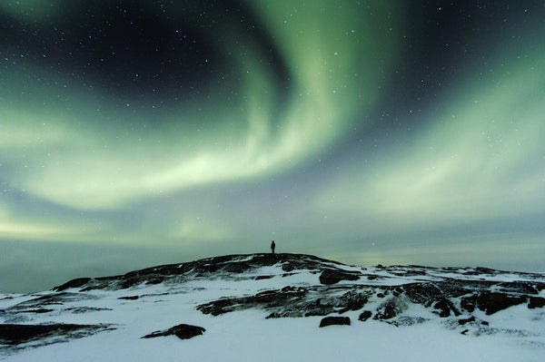 Person standing looking at the Northern Lights in Iceland