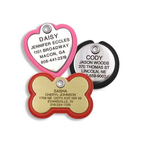stainless heart shaped tag with neon pink frame, stainless round tag with black frame, and a brass bone shaped tag with red frame