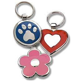 Round metal tag with blue enamel on front surrounding a metal paw design, heart shaped metal tag with red enamel on front surrounding a metal heart design, and daisy shaped metal tag with pink enamel on front