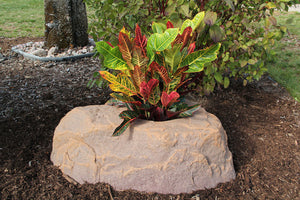 Planter Faux Rock 132 in Autumn Bluff in garden with flowers planted