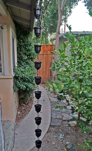 Black Naoki Cups Rain Chain on house with water flowing through multiple cups