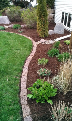 DekoRRa Block Edging Kit in flower bed with red mulch