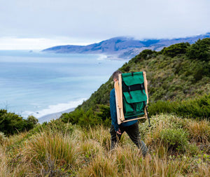 The portable Backpack Chair in forest green being taken on a hike