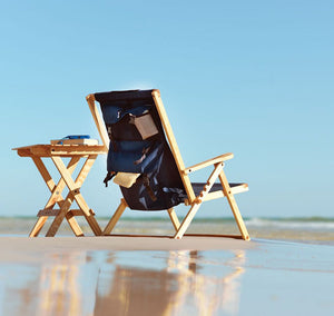The portable Backpack Chair in navy blue at beach