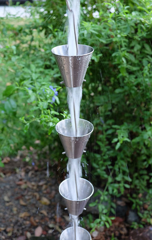 Full length image of stainless colored Steel Cups Rain Chain with water running through cups