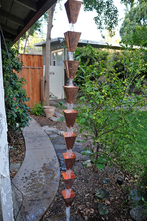 Full length image of Large Tapered Cup style rain chain in Copper with water running through cups