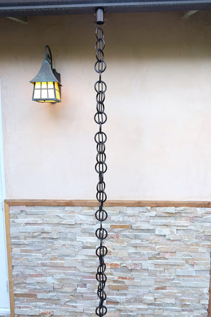 bronze Cast Zen Loops Rain Chain full length image next to home