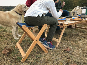 The Deluxe lightweight Folding Stool used as seat at camp