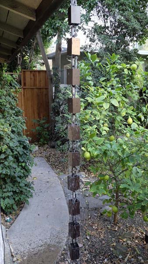 Square Kenchiku Aluminum Bronze Rain Chain on home with water running through multiple cups