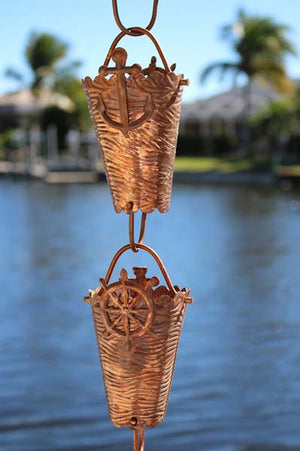 Nautical Cups Copper Rain Chain with ships wheel accent in front of water