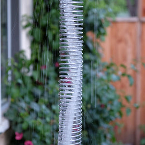 Downspout Spring rain chain with water running through it