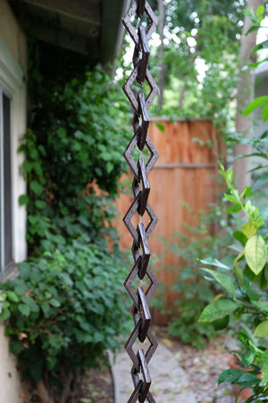 Rain water flowing down bronze Diamond Links Rain Chain on home