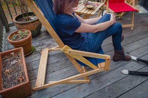 The Sling Recliner in navy blue used on deck